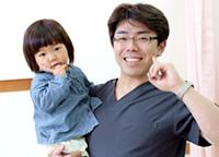 子供を抱いている柔道整復師の写真